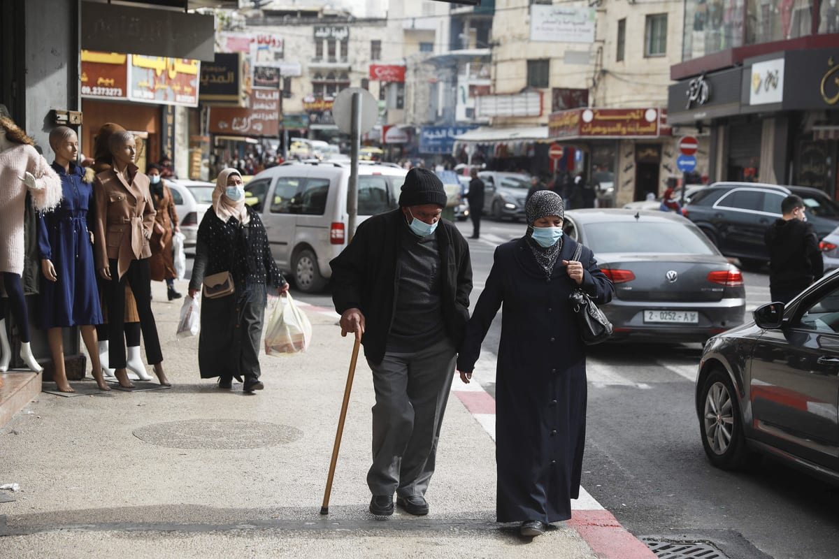 Palestinians wear face masks as a measure against the novel type of coronavirus (COVID-19) pandemic in Ramallah, West Bank on 30 January 2021 [Issam Rimawi/Anadolu Agency]