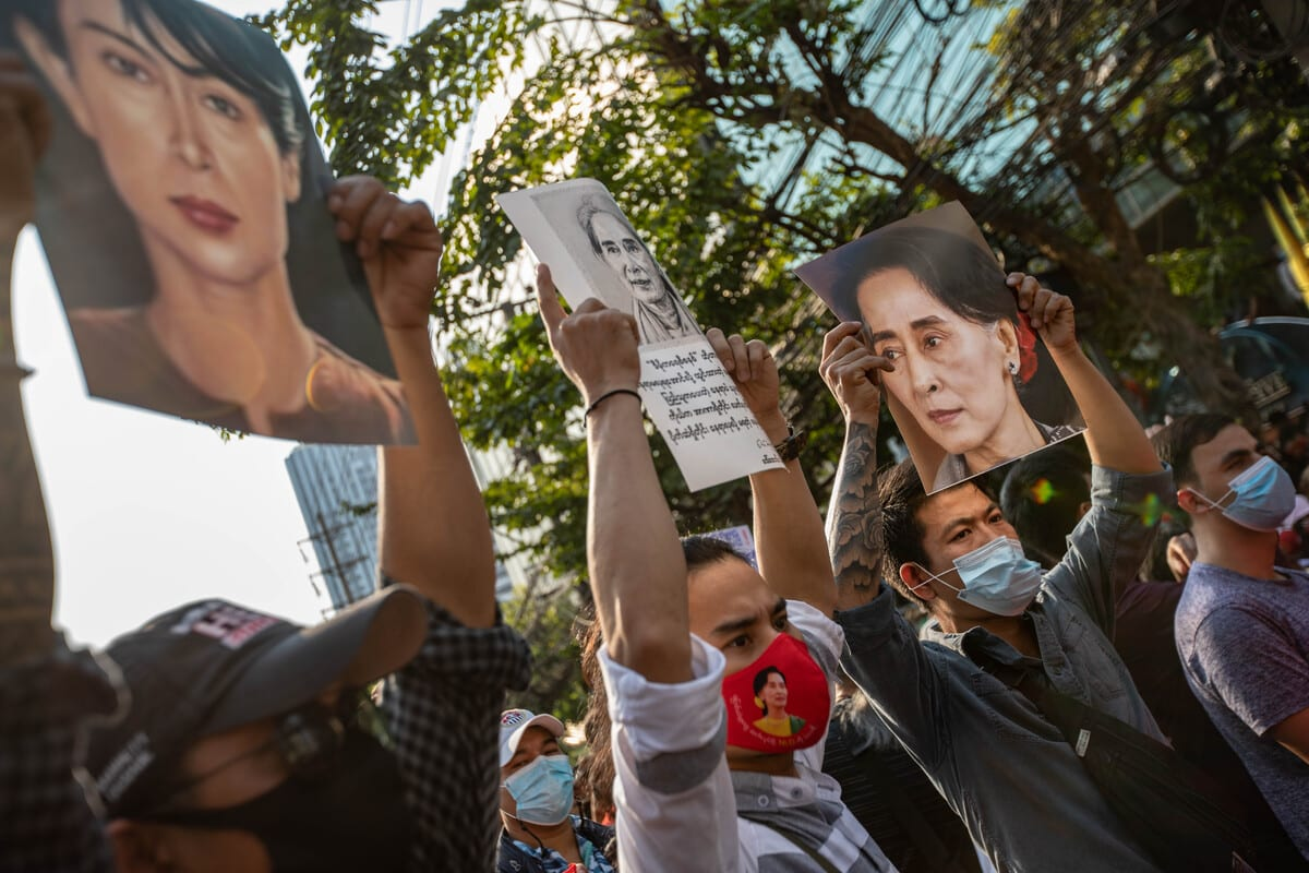 Demonstrators hold portraits of Aung San Suu Kyi during a protest outside the Embassy of Myanmar in Bangkok, Thailand on 1 February 2021. [Guillaume Payen - Anadolu Agency]