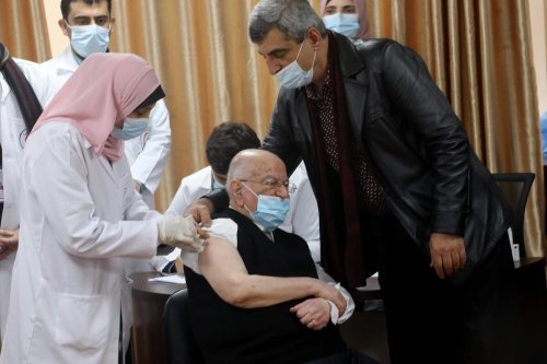 Former Palestinian Authority Minister of Health, Dr. Riyad Al-Zanoun, receives coronavirus (Covid-19) vaccine in Gaza on 22 February 2021 [Mohammed Asad/Middle East Monitor]