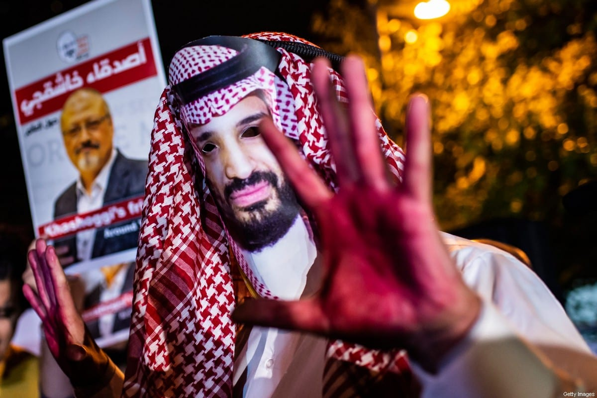 A protestor wears a mask of depicting Saudi Crown Prince Mohammad Bin Salman next to posters of the murdered Saudi journalist Jamal Khashoggi on 25 October 2018 [YASIN AKGUL/AFP/Getty Images]