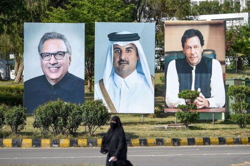 A Pakistani woman walks past the portraits of visiting Qatar's ruler Sheikh Tamim bin Hamad Al-Thani (C) along with Pakistani Prime Minister Imran Khan (R) and President Arif Alvi (L) on the Constitution Avenue in Islamabad on 21 June 2019. [FAROOQ NAEEM/AFP via Getty Images]