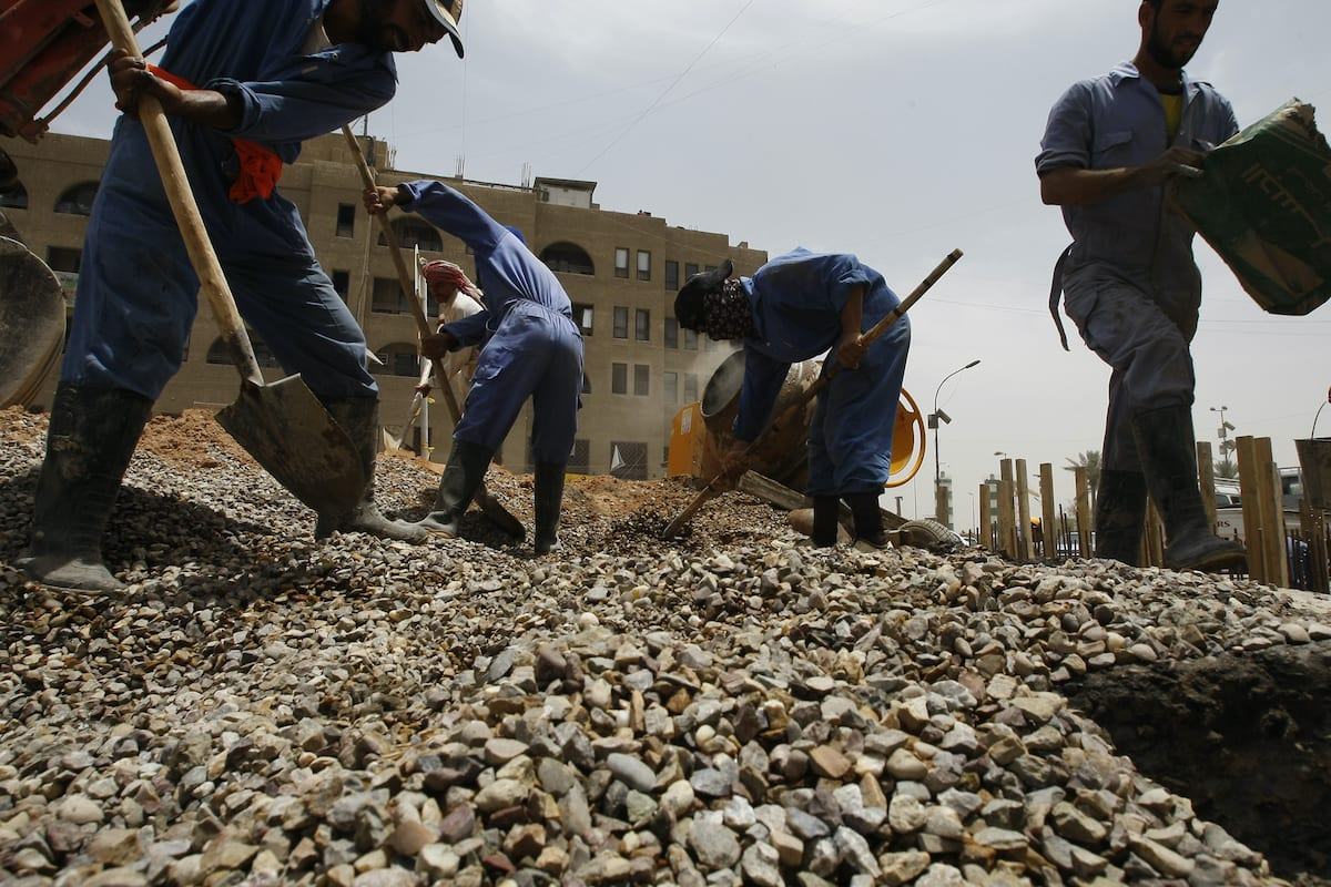 Iraqi construction workers shovel stones at a building site in Baghdad on 7 June 2011, [SABAH ARAR/AFP via Getty Images]