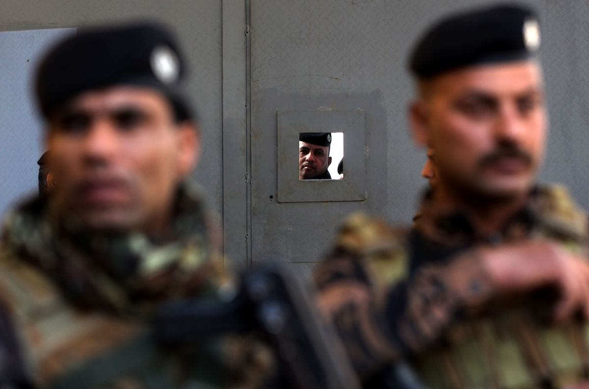 Iraqi policemen stand guard outside the Central Bank of Iraq headquarters along Rashid Street in the centre of the capital Baghdad on 22 December 2020. [AHMAD AL-RUBAYE/AFP via Getty Images]