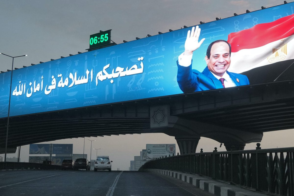 Cars drive along an overpass beneath a giant electronic billboard showing a banner by Egypt's Defence Ministry depicting President Abdel Fattah al-Sisi next to a message wishing safe travels, placed atop a second newly-constructed bridge in the Nasr City district of Egypt's capital Cairo on 15 January 2021. [AMIR MAKAR/AFP via Getty Images]