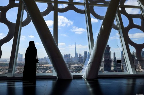 TOPSHOT - A woman looks on upon a view of downtown Dubai with the Burj Khalifa on 1 February 2021 [GIUSEPPE CACACE/AFP/Getty Images]