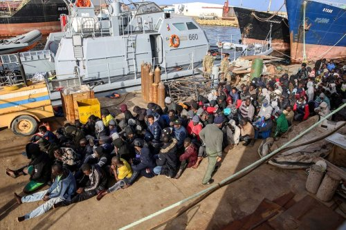 Migrants rescued off the coast of al-Khums, about 120 kilometres east of the capital, sit on the pier in Tripoli's naval base on 10 February 2021. [AFP via Getty Images]
