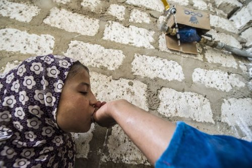 Egyptian mother cups her hands under a running tap in her yard to let her her daughter 6 drink, in the village of al-Jendaya, in the Bani Mazar province, in the Minya governorate some 200km south of Cairo on 5 April 2016. [KHALED DESOUKI/AFP via Getty Images]
