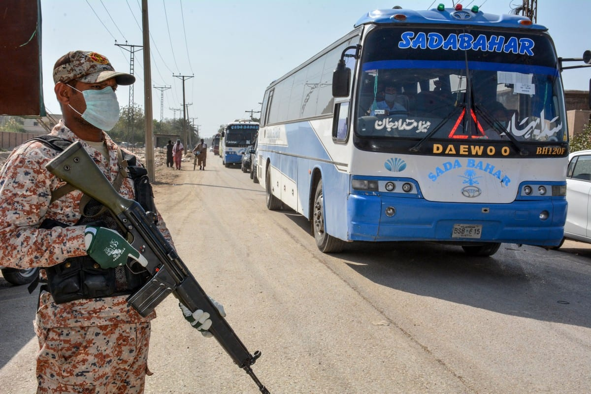 A soldier wearing a facemask stands guard as buses carry pilgrims returning from Iran via the Pakistan-Iran border town of Taftan on 18 March 2020 [SHAHID ALI/AFP/Getty Images]