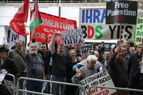 Demonstrators hold placards as they protest against antisemitism in central London on September 4, 2018 [DANIEL LEAL-OLIVAS/AFP via Getty Images]