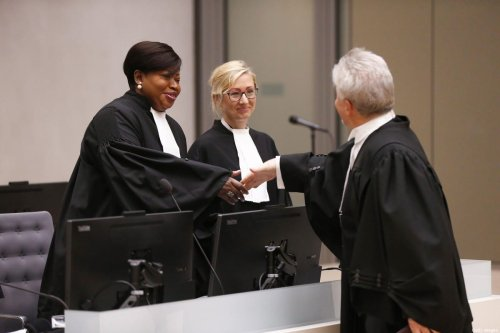 International Criminal Court's prosecutor Fatou Bensouda (L) shakes hands in the courtroom of the International Criminal Court (ICC) in The Hague, The Netherlands, on July 8, 2019 [EVA PLEVIER/AFP via Getty Images]