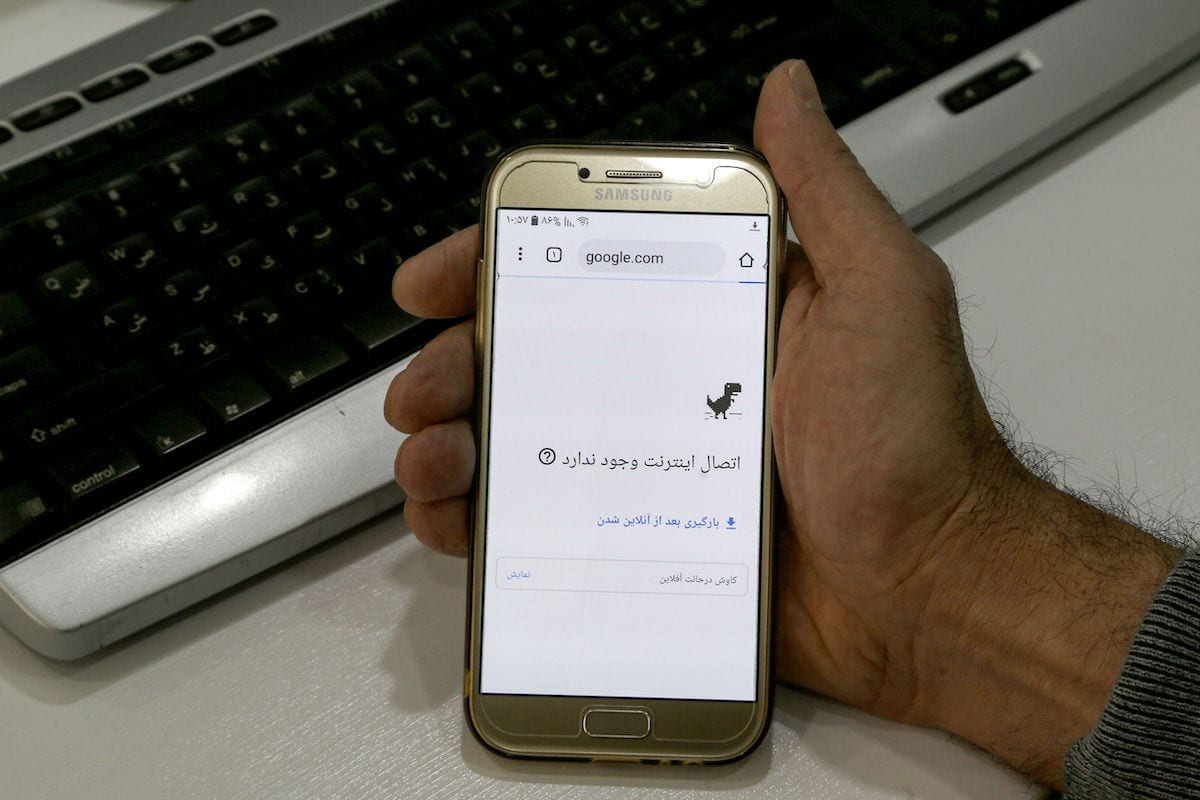 A man holds a smartphone connected to a Wifi network without internet access at an office in the Iranian capital Tehran on 17 November 2019. [ATTA KENARE/AFP via Getty Images]