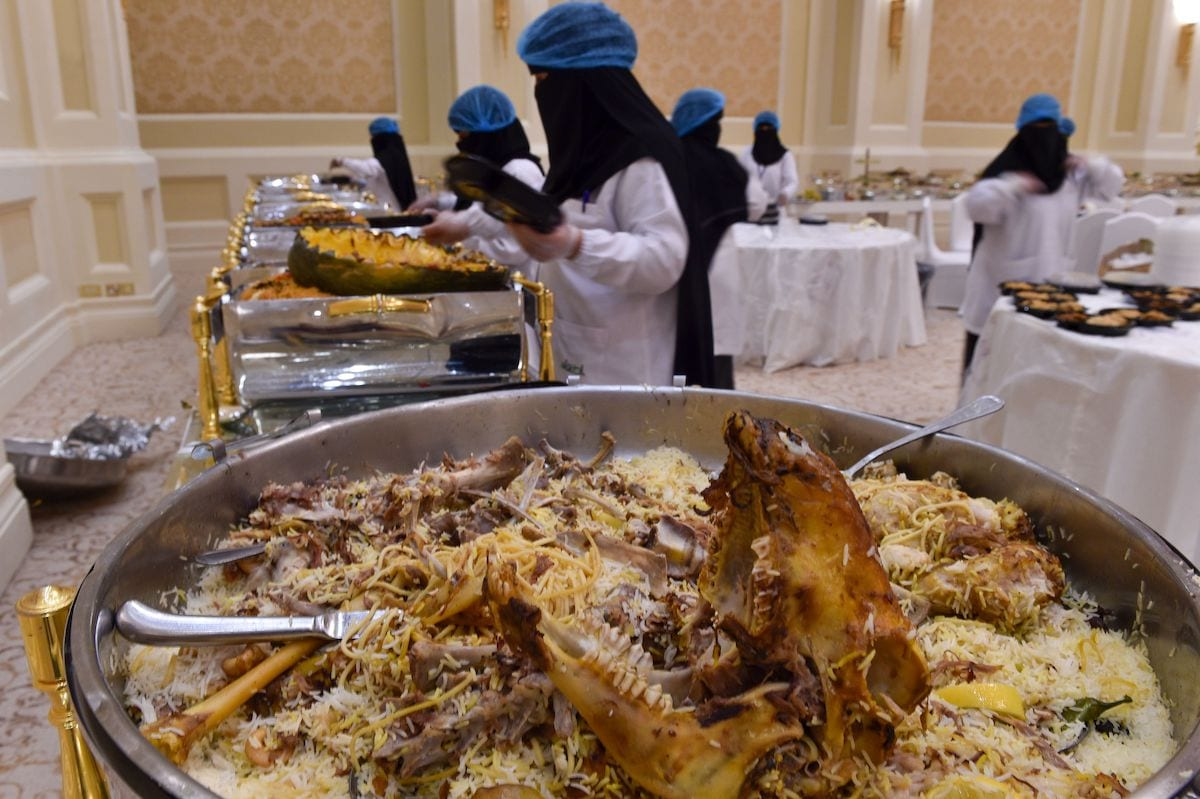 Saudi volunteers, with the Saudi Food Bank or Etaam, pack leftovers into boxes after a wedding in Riyadh on 3 July 2019. [FAYEZ NURELDINE/AFP via Getty Images]