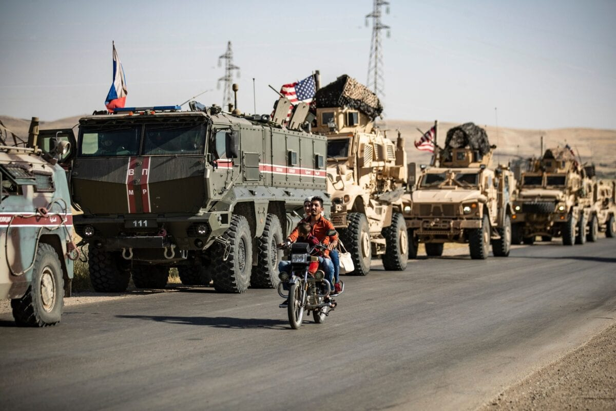 A couple ride a motorcycle past Russian and US military vehicles in the northeastern Syrian town of al-Malikiyah (Derik) at the border with Turkey, on June 3, 2020 [DELIL SOULEIMAN/AFP via Getty Images]