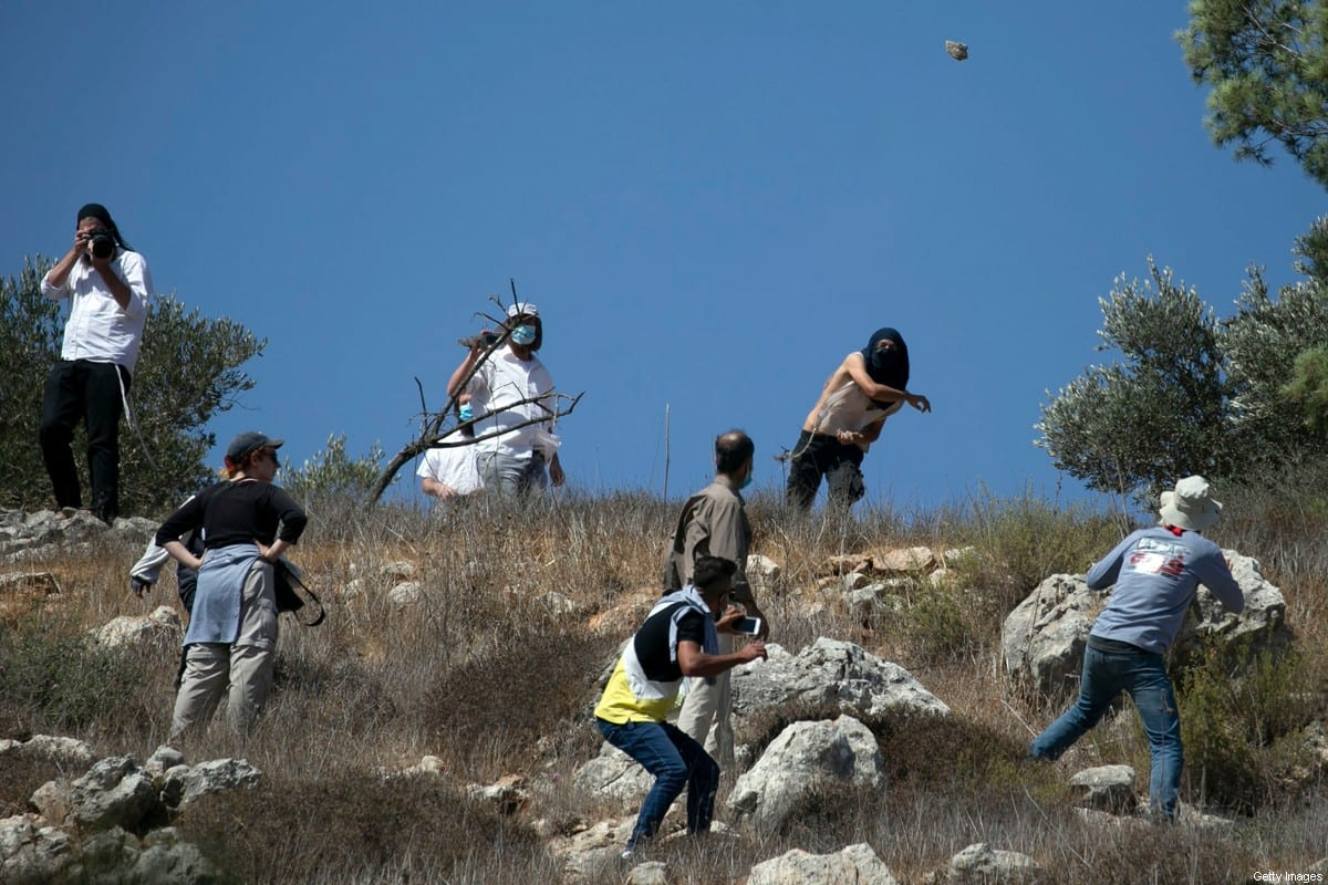 Masked Israeli settlers attack Palestinian olive farmers from the village of Hawara on fields near the settlement of Yitzhar in the Israeli-occupied West Bank, on October 7, 2020 [JAAFAR ASHTIYEH/AFP via Getty Images]