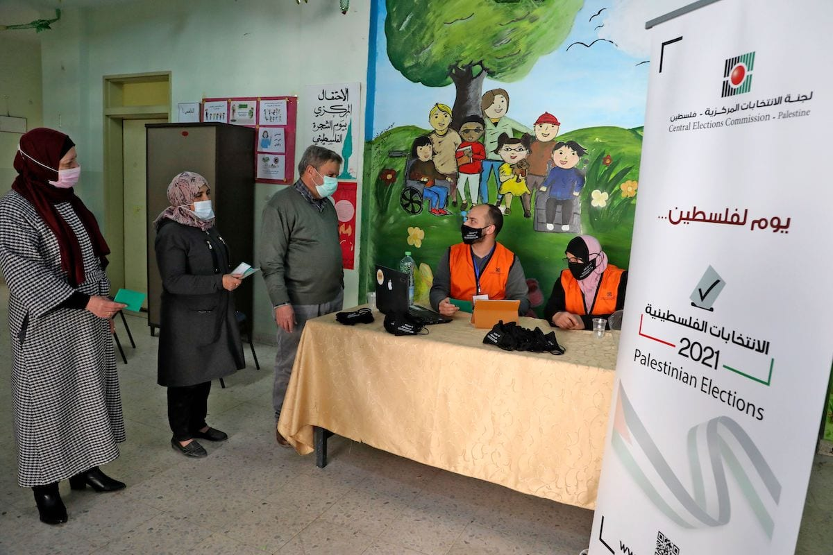 Members of the Palestinian Central Elections Commission register voters in the West Bank town of Hebron on 10 February 2021. [HAZEM BADER/AFP via Getty Images]