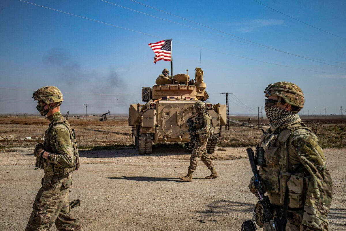 US soldiers walk while on patrol by the Suwaydiyah oil fields in Syria's northeastern Hasakah province on February 13, 2021 [DELIL SOULEIMAN/AFP via Getty Images]