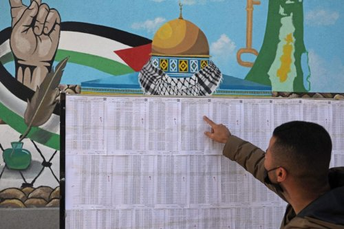 A Palestinian man looks for his name on the electoral roll at a school in Gaza City on March 3, 2021, ahead of the first Palestinian elections in 15 years [MOHAMMED ABED/AFP via Getty Images]