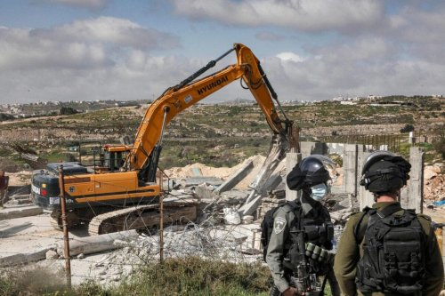 An Israeli soldier and border guard stand by as an excavator demolishes a Palestinian house located within the area C southeast of Hebron in the occupied West Bank on March 8, 2021 [HAZEM BADER/AFP via Getty Images]