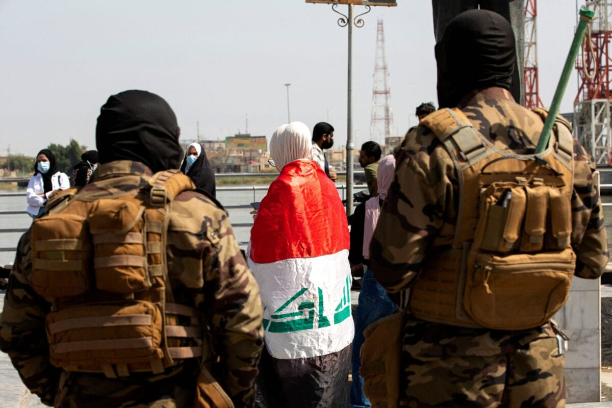 Members of Iraqi security forces look on as a demonstrator stands draped in a national flag durign a rally for International Women's Day in Iraq's southern city of Basra on March 8, 2021 [HUSSEIN FALEH/AFP via Getty Images]