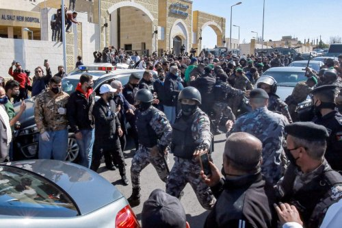 Members of Jordan's Darak forces (gendarmerie) keep demonstrators away outside al-Hussain New Salt Hospital in the town of Salt, northwest of Jordan's capital, on March 13, 2021, as people protest the deaths of of COVID-19 coronavirus patients who died of lack of oxygen [KHALIL MAZRAAWI/AFP via Getty Images]
