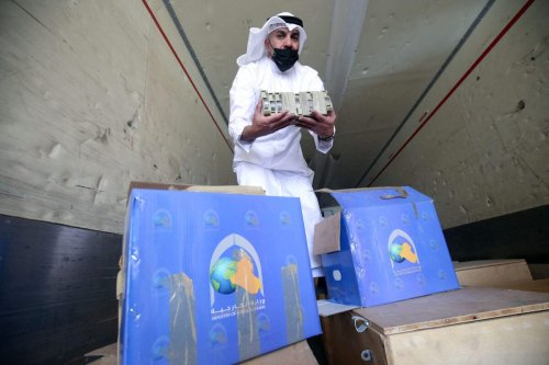 Employee at the Kuwaiti Information Ministry Essam al-Said inspects boxes in the back of a truck containing Kuwaiti archives seized during the Iraqi invasion of the Gulf emirate in 1990, after their restitution by Iraqi authorities in Kuwait City, on March 28, 2021 [YASSER AL-ZAYYAT/AFP via Getty Images]