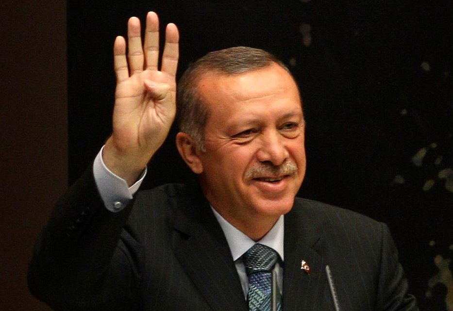 Turkey's Prime Minister Tayyip Erdogan flashes the Rabaa salute as he gives a speech during a meeting at his ruling Justice and Development Party (AKP) party headquarters in Ankara, on 20 August 2013. [ADEM ALTAN/AFP via Getty Images]