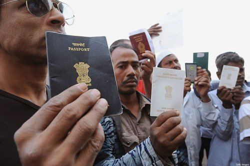 Foreign workers show their passports as they gather outside a Saudi immigration office waiting for an exit permit as Saudi security begin their search campaign against illegal laborers, on November 4, 2013 in downtown of Riyadh. A new four-month deadline ends for illegal foreign workers to regularise their status, leave the country, or risk imprisonment. AFP PHOTO/FAYEZ NURELDINE (Photo credit should read FAYEZ NURELDINE/AFP via Getty Images)