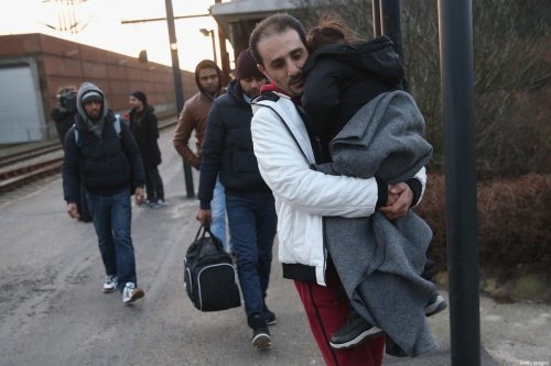 PADBORG, DENMARK - JANUARY 06: Migrants, many of them from Syria, walk to police vans after police found them while checking the identity papers of passengers on a train arriving from Germany on January 6, 2016 in Padborg, Denmark. Denmark introduced a 10-day period of passport controls and spot checks on Monday on its border to Germany in an effort to stem the arrival of refugees and migrants seeking to pass through Denmark on their way to Sweden. Denmark reacted to border controls introduced by Sweden the same day and is seeking to avoid a backlog of migrants accumulating in Denmark. Refugees still have the right to apply for asylum in Denmark and those caught without a valid passport or visa who do not apply for asylum are sent back to Germany. (Photo by Sean Gallup/Getty Images)