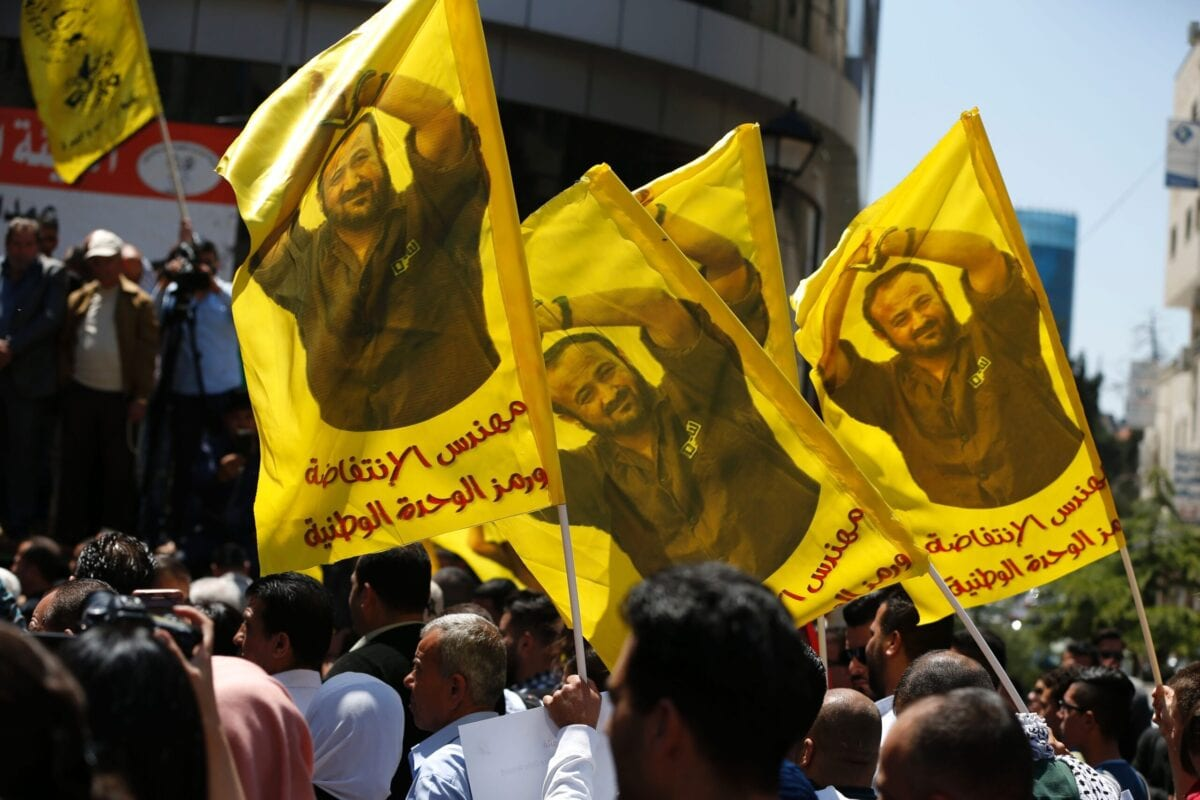 Protesters wave flags bearing a portrait of prominent jailed Palestinian Marwan Barghouti during a rally in the West Bank city of Ramallah on April 17, 2017 [ABBAS MOMANI/AFP via Getty Images]