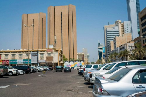 Automobiles stand in a parking lot near retail stores and office towers in Kuwait City, Kuwait, on Sunday, Aug. 13, 2017 [Tasneem Alsultan/Bloomberg via Getty Images]