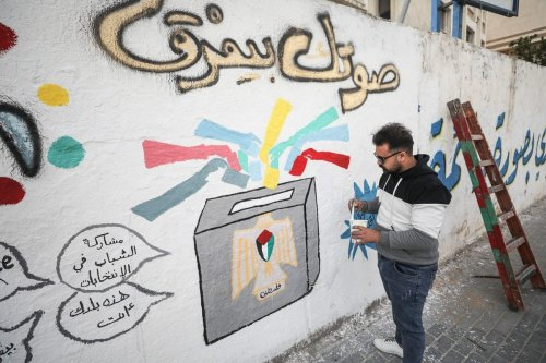Palestinian artist paints an election related graffiti on a wall ahead of elections for the Palestinian Legislative Council in Gaza City, Gaza on 24 March 2021 [Mustafa Hassona/Anadolu Agency]
