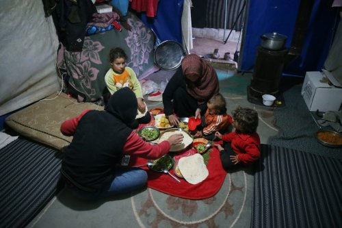A Syrian family gathers to break their fasts on the first day of Ramadan at Ma'arrat Misrin camp away from their home in Idlib, Syria on April 13, 2021 [Ahmet Karaahmet/Anadolu Agency]