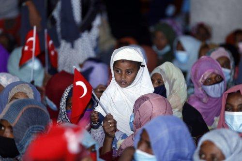 Ethiopian women and children holding Turkish flags after a Turkish charity donated aid in Addis Ababa, Ethiopia on 17 April 2021 [Minasse Wondimu Hailu/Anadolu Agency]