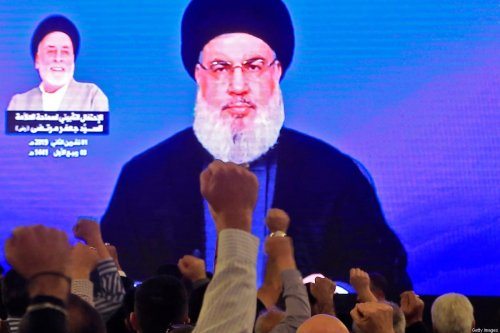 Supporters of Hassan Nasrallah, the head of Lebanon's militant Shiite Muslim Hezbollah movement, watch him speak through a giant screen at a mosque in Beirut on 1 November 2019 [AFP/Getty Images]
