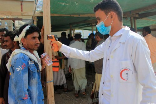 A healthcare worker checks the temperature of displaced Yemenis amid the COVID-19 pandemic, as they arrive to receive humanitarian aid provided by the World Food Programme (WFP) in the northern province of Hajjah, on January 12, 2021. (Photo by ESSA AHMED / AFP) (Photo by ESSA AHMED/AFP via Getty Images)