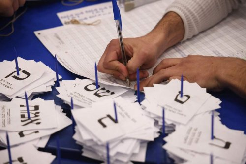 Electoral workers count ballots in Israel's general elections in Jerusalem on 25 March 2021. [EMMANUEL DUNAND/AFP via Getty Images]