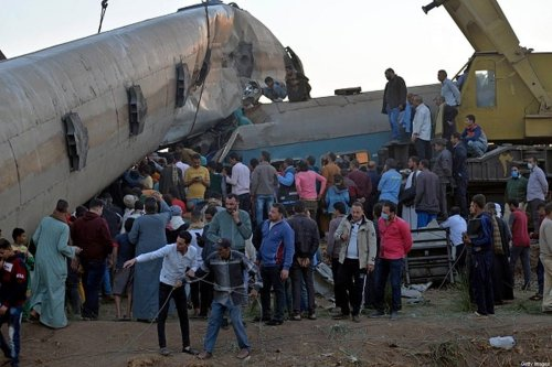 People gather around the wreckage of two trains that collided in the Tahta district of Sohag province, some 460 kilometres (285 miles) south of the Egyptian capital Cairo, reportedly killing at least 19 people and injuring scores of others, on March 26, 2021 [AFP via Getty Images]