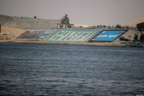 """A """"Welcome to Egypt"""" sign can be seen across the Suez Canal on 30 March 2021 in Ismailia, Egypt. [Mahmoud Khaled/Getty Images]"""