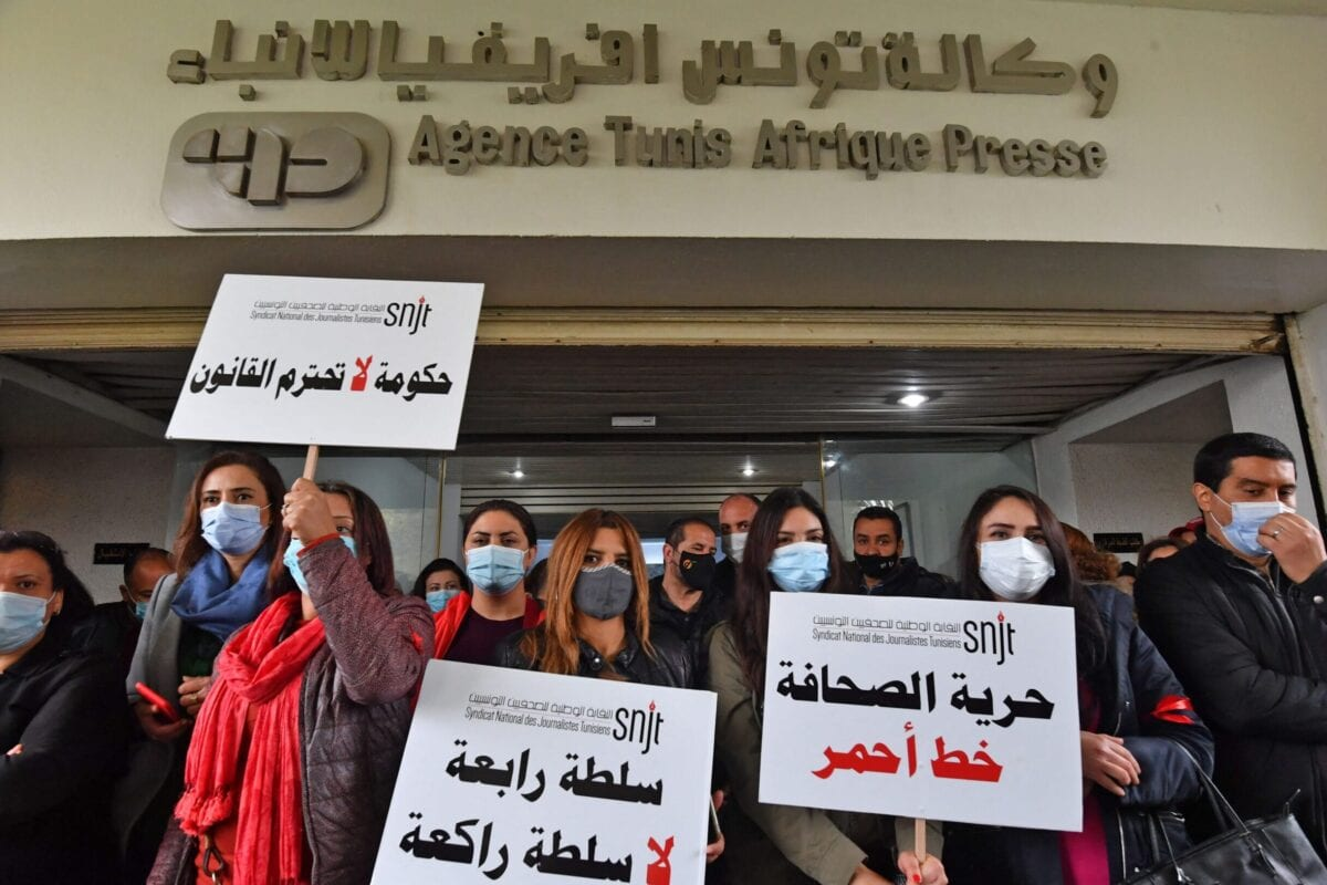 Journalists hold up signs as they gather for a demonstration outside the headquarters of Tunisia's national Tunis Afrique Presse (TAP) news agency in the capital on April 15, 2021 [FETHI BELAID/AFP via Getty Images]