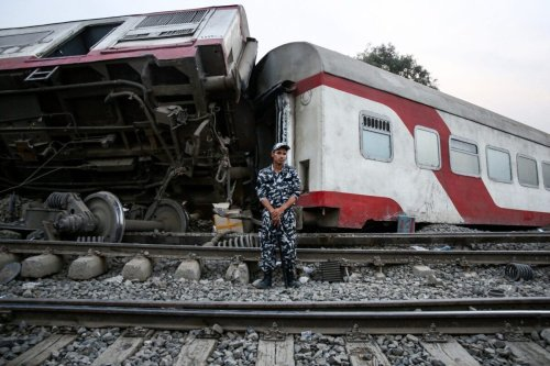 A member of Egyptian security forces stands guard before an overturned passenger carriage at the scene of a railway accident in the city of Toukh in Egypt's central Nile Delta province of Qalyubiya on April 18, 2021 [AYMAN AREF/AFP via Getty Images]
