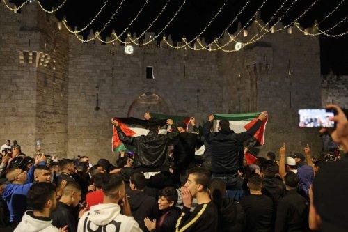 Palestinians wave the national flag outside the Damascus Gate in Jerusalem's Old City on April 27, 2021 [MENAHEM KAHANA/AFP via Getty Images]