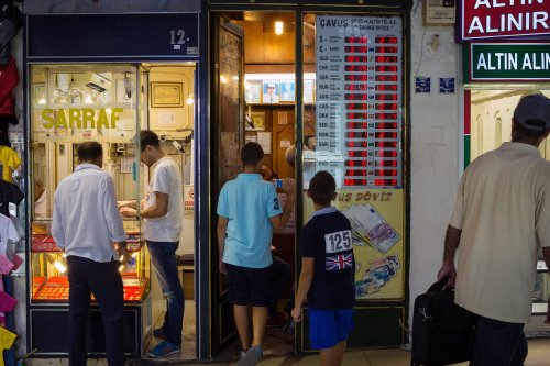 Customers browse gold jewelry on display in the window of a store as others queue to use a foreign currency exchange bureau in the Grand Bazaar's gold souk in Istanbul, Turkey, on Saturday, August 15, 2015 [Kerem Uzel/Bloomberg via Getty Images]