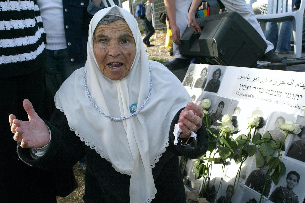 A Palestinian survivor reacts during a memorial ceremony at the original site of her former village of Deir Yassin in Jerusalem, on 07 April 2005 [ATTA HUSSEIN/AFP via Getty Images]