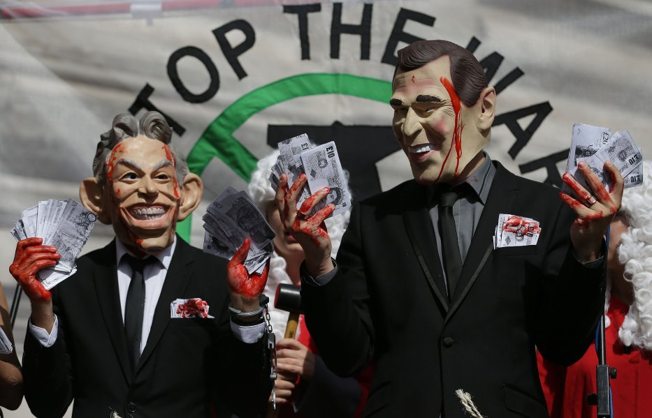 Demonstrators wearing masks depicting former British Prime Minister Tony Blair (L) and former US President George W. Bush protest outside QEII Centre in London on July 6, 2016 [DANIEL LEAL-OLIVAS/AFP via Getty Images]