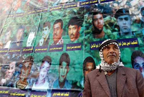 Standing in front of posters showing the victims of the Jenin refugee camp massacre in 2002 by Israeli troops [SAIF DAHLAH/AFP via Getty Images]