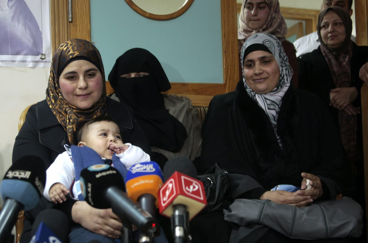 Dallal Ziben, 32, carries her baby muhannad as she attends a press conference to announce for the succes artificial insemination operations after smuggling sperm samples from four Palestinian prisoners, in the West Bank city of Nablus on 6 Feb. 2013. [Nedal Eshtayah/Apaimages]
