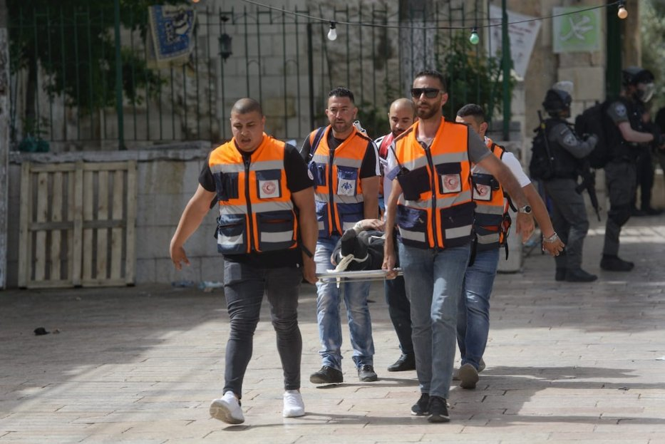 JERUSALEM - MAY 10: Palestinian medics treat an injured youth after Israeli police's intervention as Palestinians guard to prevent fanatic Jews to raid the Masjid al-Aqsa Compound, in East Jerusalem on May 10, 2021. ( Muath Khatib - Anadolu Agency )