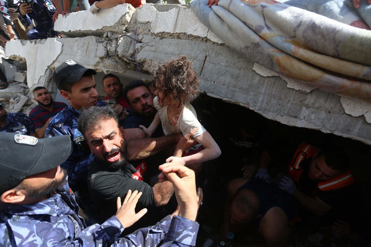 People rescue a wounded child from a debris as search and rescue works continue at a debris of a building after airstrikes by Israeli army hit buildings in al-Rimal neighborhood of Gaza City, Gaza on 16 May 2021. [Ashraf Amra - Anadolu Agency]