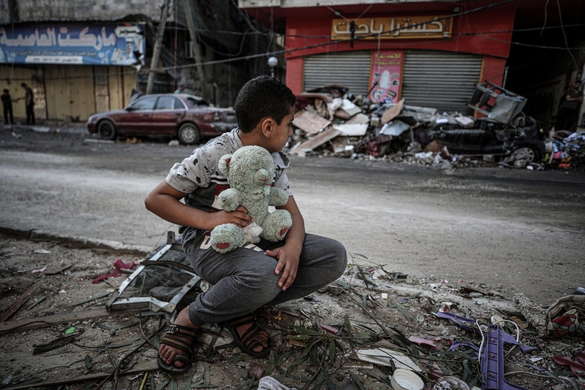 A boy is seen with his teddy bear after his home was damaged Israeli air strikes in Gaza on 19 May 2021 [Ali Jadallah/Anadolu Agency]
