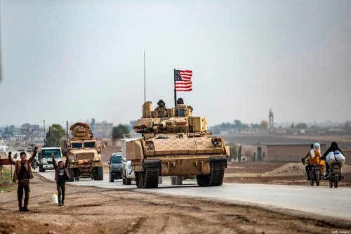 Children gesture as US troops patrol in their military vehicles on the roads of the Syrian town of al-Jawadiyah and meet the inhabitants, in the northeastern Hasakeh province, near the border with Turkey, on December 17, 2020 [DELIL SOULEIMAN/AFP via Getty Images]